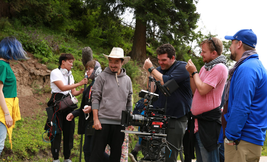 "Assistant Director Huang Yang (center, in cowboy hat) as the crew learns to make the ""heart"" gesture for photos"